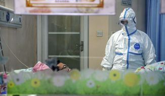In this Thursday, Jan. 30, 2020, file photo, a doctor attends to a patient in an isolation ward at a hospital in Wuhan in central China's Hubei Province. Foreign evacuees from China's worst-hit region returned home to medical observation and even isolation. (Chinatopix via AP, File)