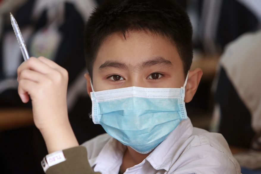 A student wears a protective face mask in during class at the Dinh Cong secondary school in Hanoi, Vietnam on Friday, Jan. 31, 2020. The authorities have advised students to wear masks to school, a day after Vietnam confirmed three more cases of the new virus. (AP Photo/Hau Dinh)