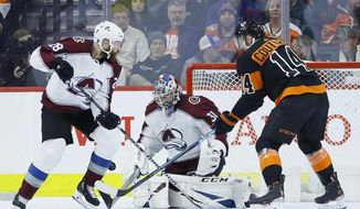 Colorado Avalanche's Philipp Grubauer (31) blocks a shot as Ian Cole (28) and Philadelphia Flyers' Sean Couturier (14) look on during the first period of an NHL hockey game, Saturday, Feb. 1, 2020, in Philadelphia. (AP Photo/Matt Slocum)