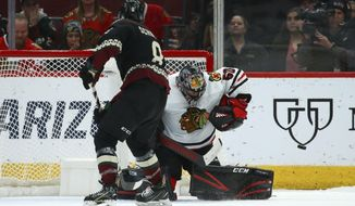 Chicago Blackhawks goaltender Corey Crawford (50) makes a save on a shot from Arizona Coyotes center Nick Schmaltz (8) during a shootout in an NHL hockey game Saturday, Feb. 1, 2020, in Glendale, Ariz. (AP Photo/Ross D. Franklin)