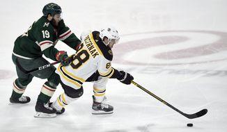 Boston Bruins' David Pastrnak (88), of the Czech Republic, has the puck against Minnesota Wild's Luke Kunin (19) during the first period of an NHL hockey game Saturday, Feb. 1, 2020, in St. Paul, Minn. (AP Photo/Hannah Foslien)