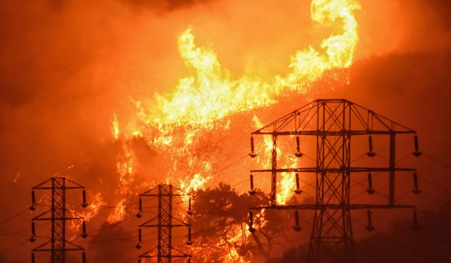 FILE - This Dec. 16, 2017, file photo provided by the Santa Barbara County Fire Department shows flames burning near power lines in Montecito, Calif. Pacific Gas and Electric is promising promising to overhaul its board of directors in an attempt to avoid a potential takeover attempt by the state of California and prove the beleaguered utility is turning over a new leaf as it works through its second bankruptcy in less than 20 years. The promise to shake things up came late Friday, Jan. 31, 2020, as the San Francisco company tries to emerge from bankruptcy by June 30. (Mike Eliason/Santa Barbara County Fire Department via AP, File)