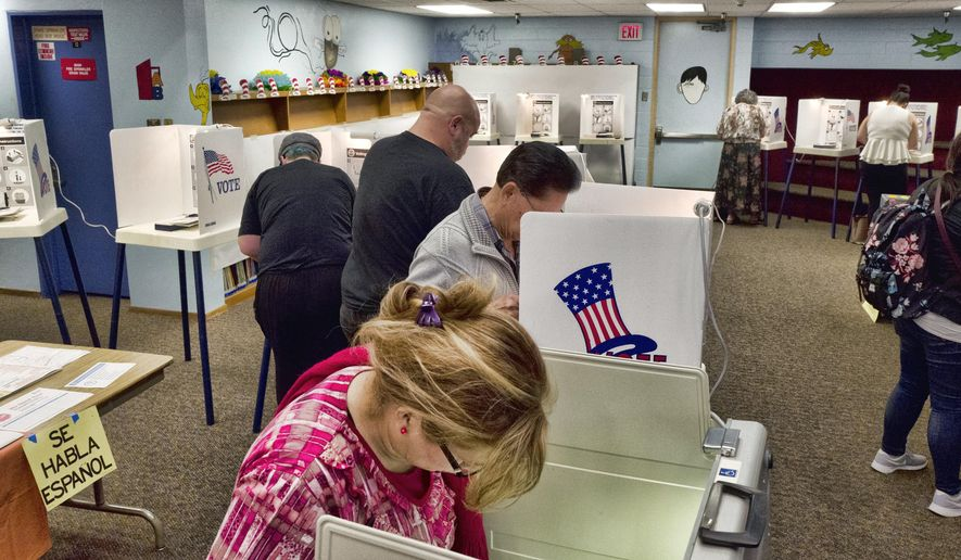 In this June 5, 2018, file photo, voters mark ballots at a polling place in the library at the Robert F. Kennedy Elementary School in Los Angeles. Californians start voting Monday, Feb. 3, 2020, in a high-profile Democratic presidential primary that has no clear front-runner. For the first time, Californians can register to vote on election day at the polls. (AP Photo/Richard Vogel, File)