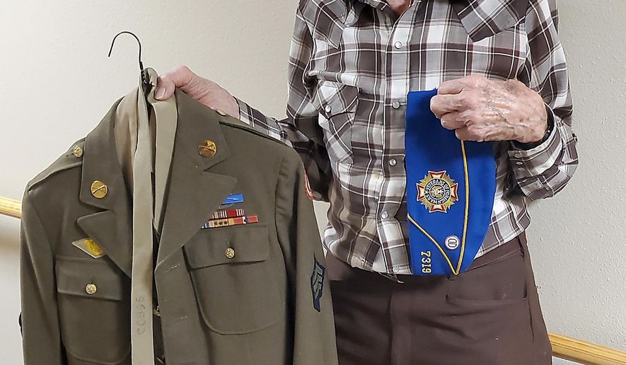Allen Gibbs shows off his uniform from his service in the army in World War II in Rapid City, S.D.. Allen Gibbs doesn't consider himself a hero. The 98-year-old veteran has been called a hero many times in his life, but he will tell you he doesn't deserve the title compared to others he served with in World War II.  (Kent Bush/Rapid City Journal via AP)
