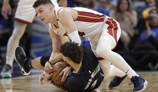 Miami Heat guard Tyler Herro, top right, goes after the ball against Orlando Magic guard Michael Carter-Williams, bottom, during the first half of an NBA basketball game, Saturday, Feb. 1, 2020, in Orlando, Fla. (AP Photo/John Raoux)
