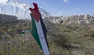 """Protesters post a placard with the colors of the Palestinian flags and Arabic that reads """"Jerusalem is the eternal capital of Palestine,"""" at a barbed wire surrounding the Israeli separation wall and the Israeli settlement of Mod'in Ilit, background, during a protest against Israel and the Untied States in the West Bank village of Bil'in, near Ramallah, Friday, Jan. 31, 2020. (AP Photo/Nasser Nasser)"""