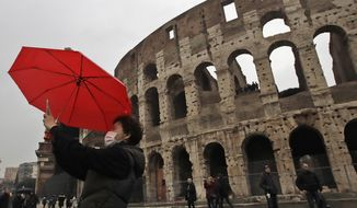 A tourist wearing a mask takes a selfie in front of Rome's ancient Colosseum, Saturday, Feb. 1, 2020. Italy banned all flights coming from and going to China as European countries have stepped up their response to the new virus that has sickened thousands of people in China and reached 19 other countries. Italy has reported two cases.  (AP Photo/Alessandra Tarantino)