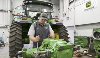 In this Dec. 4, 2019, photo Peyton Schwerdtfeger of Lyons, Kansas, works on John Deere equipment as part of the Garden City, Kansas Community College's associate degree program in Garden City. Students in Kansas can enroll in the free-tuition agricultural tech program at Garden City and Fort Scott community colleges as long as they find a John Deere dealership to sponsor them. (Alice Mannette/Hutchinson News via AP)