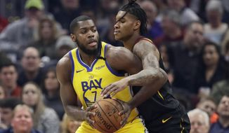 Golden State Warriors' Eric Paschall, left drives past Cleveland Cavaliers' Kevin Porter Jr. in the first half of an NBA basketball game, Saturday, Feb. 1, 2020, in Cleveland. (AP Photo/Tony Dejak)