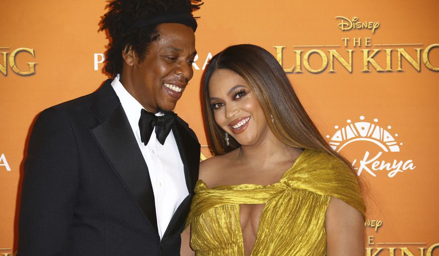 "Singers Jay-Z, left, and Beyonce pose for photographers upon arrival at the ""Lion King"" European premiere in central London. (Photo by Joel C Ryan/Invision/AP, File)"