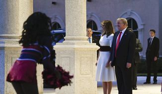 President Donald Trump and first lady Melania Trump, and their son Barron Trump, right, watch as the Florida Atlantic University Marching Band performs during a Super Bowl party at the Trump International Golf Club in West Palm Beach, Fla., Sunday, Feb. 2, 2020. (AP Photo/Susan Walsh)