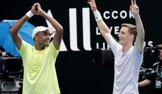 Rajeev Ram, left, of the U.S. and partner Britain's Joe Salisbury celebrate after defeating Australia's Max Purcell and Luke Saville in the men's doubles final at the Australian Open tennis championship in Melbourne, Australia, Sunday, Feb. 2, 2020. (AP Photo/Lee Jin-man)