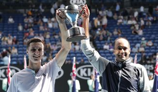 Rajeev Ram, right, of the U.S. and partner Britain's Joe Salisbury hold their trophy aloft after defeating Australia's Max Purcell and Luke Saville in the men's doubles final at the Australian Open tennis championship in Melbourne, Australia, Sunday, Feb. 2, 2020. (AP Photo/Lee Jin-man)