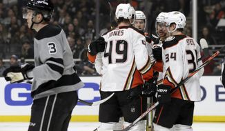 Los Angeles Kings defenseman Matt Roy, left, skates by as Anaheim Ducks celebrate a goal by Max Jones (49) during the first period of an NHL hockey game in Los Angeles, Saturday, Feb. 1, 2020. (AP Photo/Alex Gallardo)
