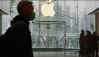 A man wearing a face mask walks past an Apple store in Hong Kong, Sunday, Feb, 2, 2020. Apple is temporarily closing its 42 stores in mainland China, one of its largest markets, as a new virus spreads rapidly. (AP Photo/Vincent Yu)