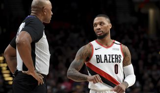 Portland Trail Blazers guard Damian Lillard, right, speaks with referee Kevin Cutler, left, during the first half of an NBA basketball game against the Utah Jazz in Portland, Ore., Saturday, Feb. 1, 2020. (AP Photo/Steve Dykes)