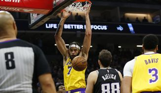 Los Angeles Lakers center JaVale McGee hangs from the rim after a dunk in front of Sacramento Kings forward Nemanja Bjelica during the first quarter of an NBA basketball game in Sacramento, Calif., Saturday, Feb. 1, 2020. (AP Photo/Rich Pedroncelli)