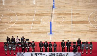 City officials and Olympic organizers pause for photos before cutting the ribbon during a grand opening ceremony of the Ariake Arena, a venue for volleyball at the Tokyo 2020 Olympics and wheelchair basketball during the Paralympic Games, Sunday, Feb. 2, 2020, in Tokyo. (AP Photo/Jae C. Hong)