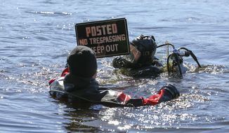 Hillsborough County Sheriff's Deputy Alton Smith, left, and Deputy Andrew Lynch, members of the HCSO Underwater Recovery Team display a sign found in the lake during a search Wednesday, Jan. 22, 2020 at Bay Tree Farm in Odessa, Fla. Members of the Hillsborough County Sheriff's Department Underwater Recovery Team and USF searched a lake, pond and property for Keystone Memorial Cemetery.  (Chris Urso/Tampa Bay Times via AP)