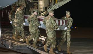FILE - In a Dec. 8, 2019 file photo, an Air Force carry team moves a transfer case containing the remains of Navy Ensign Joshua Watson, at Dover Air Force Base, Del.  Al-Qaida's branch in Yemen claimed responsibility Sunday, Feb. 2, 2020 for last year's deadly shooting at the Naval Air Station Pensacola by an aviation student from Saudi Arabia. The shooter, 2nd Lt. Mohammed Saeed Alshamrani, was a member of the Saudi Air Force in training at the base. (AP Photo/Cliff Owen, File)