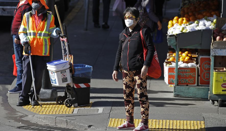 A masked worker and shopper wait for a street signal Friday, Jan. 31, 2020, in the Chinatown district in San Francisco. As China grapples with the growing coronavirus outbreak, Chinese people in California are encountering a cultural disconnect as they brace for a possible spread of the virus in their adopted homeland. (AP Photo/Ben Margot)