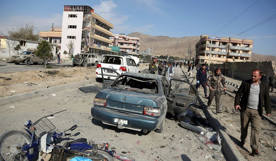 In this Wednesday, Nov. 13, 2019, file photo, Afghan security personnel gather at the site of a car bomb attack in Kabul, Afghanistan.  (AP Photo/Rahmat Gul, File) **FILE**
