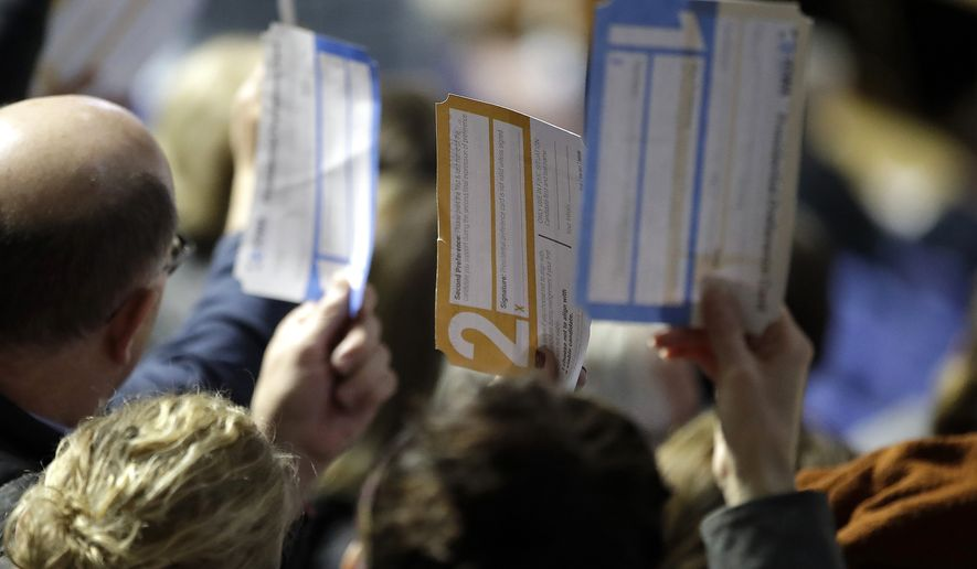 Caucus goers seated in the section for Democratic presidential candidate former Vice President Joe Biden hold up their first votes as they are counted at the Knapp Center on the Drake University campus in Des Moines, Iowa, Monday, Feb. 3, 2020. (AP Photo/Gene J. Puskar)