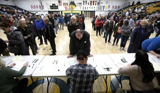Local residents check-in after arriving at an Iowa Democratic caucus at Hoover High School, Monday, Feb. 3, 2020, in Des Moines, Iowa. (AP Photo/Charlie Neibergall)