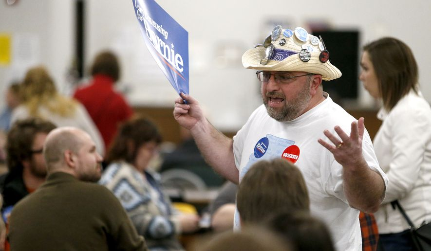 Observer David Soll of Rockford, Ill., talks to participants during the Democratic caucus at the Tri-State Independent Blind Society in Dubuque, Iowa, on Monday, Feb. 3, 2020. (Dave Kettering/Telegraph Herald via AP)