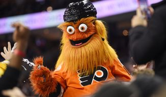In this Monday, Jan. 13, 2020, photo, the Philadelphia Flyers' mascot, Gritty, performs during an NHL hockey game in Philadelphia. Philadelphia police said Gritty has been cleared of allegations that he assaulted a 13-year-old boy during a photo shoot in November 2019. (AP Photo/Derik Hamilton,) **FILE**