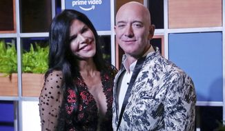In this Jan. 16, 2020, file photo, Amazon CEO Jeff Bezos, right and his girlfriend Lauren Sanchez poses for photographs during a blue carpet event organized by Amazon Prime Video in Mumbai, India. Michael Sanchez, the brother of Jeff Bezos's girlfriend, is suing the Amazon founder for defamation, alleging that Bezos and his team falsely told reporters that he provided nude photos of Bezos to the The National Enquirer.  (AP Photo/Rafiq Maqbool, File)