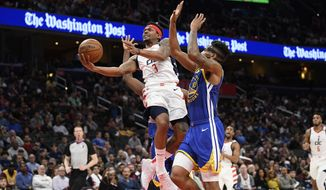 Washington Wizards guard Bradley Beal (3) goes to the basket next to Golden State Warriors guard Jacob Evans (10) during the second half of an NBA basketball game, Monday, Feb. 3, 2020, in Washington. Evans was called for a foul on the play. The Warriors won 125-117. (AP Photo/Nick Wass) ** FILE **