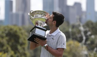 Serbia's Novak Djokovic kisses his trophy, the Norman Brookes Challenge Cup, during a photo shoot at Melbourne's Royal Botanic Gardens following his win over Austria's Dominic Thiem in the men's singles final at the Australian Open tennis championships, in Melbourne, Australia, Monday, Feb. 3, 2020. (AP Photo/Dita Alangkara)