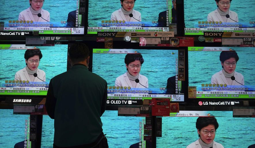 A man wears protective face masks stands in front of TV screens broadcasting Hong Kong Chief Executive Carrie Lam delivering a speech in Hong Kong, Monday, Feb. 3, 2020. Lam says the city will shut almost all land and sea border control points to the mainland from midnight to stem the spread of the novel coronavirus from China. (AP Photo/Vincent Yu)