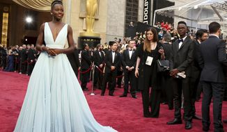 "FILE - This March 2, 2014 file photo shows Lupita Nyong'o in a pale blue Prada dress at the Oscars in Los Angeles. What happens to the duds after a big awards night can be a peculiar affair that depends on the relationship a celebrity has with a designer. Nyong'o, who won the Oscar for best supporting actress for ""12 Years a Slave,"" was able to keep her gown. (Photo by Matt Sayles/Invision/AP, File)"