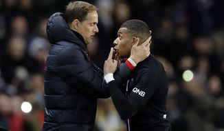 PSG's Kylian Mbappe, right, talks with PSG's head coach Thomas Tuchel during the French League One soccer match between Paris-Saint-Germain and Montpellier at the Parc des Princes stadium in Paris, Saturday Feb. 1, 2020. (AP Photo/Christophe Ena)