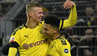 Dortmund's scorer Erling Haaland celebrates with Jadon Sancho, right, after he scored his side's 5th goal during the German Bundesliga soccer match between Borussia Dortmund and 1. FC Cologne in Dortmund, Germany, Friday, Jan. 24, 2020. Dortmund defeated Cologne with 5-1, Haaland scored twice. (AP Photo/Martin Meissner)