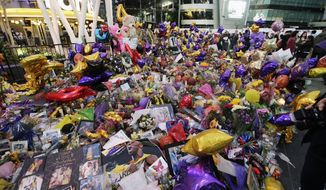 Fans gather at a memorial for the late Kobe Bryant in front of Staples Center in Los Angeles, Sunday, Feb. 2, 2020. Bryant, the 18-time NBA All-Star who won five championships and became one of the greatest basketball players of his generation during a 20-year career with the Lakers, died in a helicopter crash Sunday, Jan. 26. (AP Photo/Damian Dovarganes)