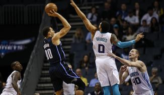 Orlando Magic forward Aaron Gordon (00) shoots over Charlotte Hornets forward Miles Bridges (0) as Charlotte Hornets guard Terry Rozier, left, and Charlotte Hornets center Cody Zeller, right, look on in the first half of an NBA basketball game in Charlotte, N.C., Monday, Feb. 3, 2020. (AP Photo/Nell Redmond)