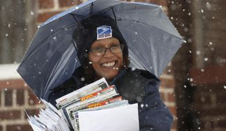 Mail carrier Tina Fisher uses an umbrella attached to her hat while delivering to her route as a winter storm drifts over the Intermountain West, Monday, Feb. 3, 2020, in Denver. Forecasters are predicting more than six inches of snow in the Denver metropolitan area and up to a foot in some mountain reporting locations before the storm moves east and on to the Great Plains on Tuesday. (AP Photo/David Zalubowski)