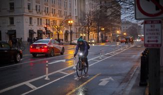 A bicyclist use the bicycle lane on 15th Street near the White House in Washington as snow begins to fall, Saturday, Feb. 17, 2018.  (AP Photo/Pablo Martinez Monsivais)  **FILE**