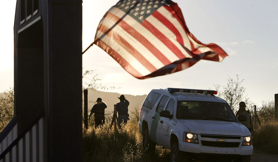 In this Dec. 15, 2010, file photo, an American flag on a nearby resident's home waves in the breeze near a U.S. Border Patrol truck blocking the road leading to a search area near where Border Patrol Agent Brian Terry was killed northwest of Nogales, Ariz. (Greg Bryan/Arizona Daily Star via AP, File)