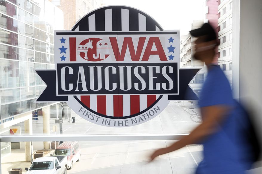 A pedestrian walks past a sign for the Iowa Caucuses on a downtown skywalk, Tuesday, Feb. 4, 2020, in Des Moines, Iowa. (AP Photo/Charlie Neibergall)