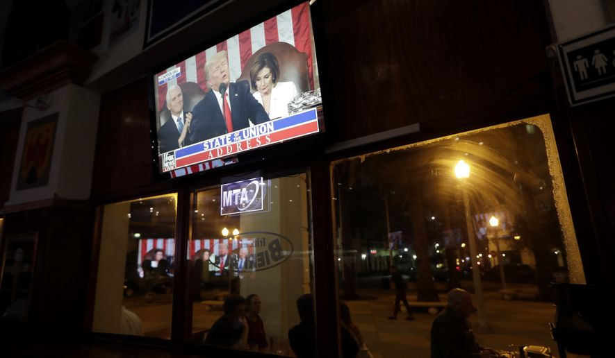 A television shows President Donald Trump as he delivers the State of the Union address to a joint session of Congress, during a watch party hosted by Miami Young Republicans and Trump Victory Miami, Tuesday, Feb. 4, 2020, in Coral Gables, Fla. (AP Photo/Lynne Sladky)