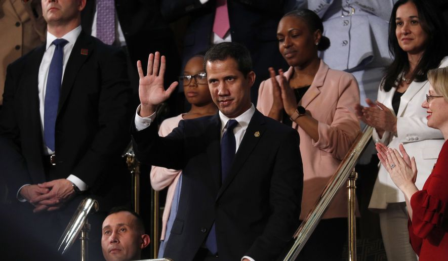 Venezuelan opposition leader Juan Guaido waves as President Donald Trump delivers his State of the Union address to a joint session of Congress on Capitol Hill in Washington, Tuesday, Feb. 4, 2020. (Leah Millis/Pool via AP)