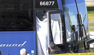 Coroner's officials work behind a drape to remove the body of a person who was killed when a gunman opened fire aboard a packed Greyhound bus, and wounded five others before the driver pulled over onto the shoulder and the killer got off, in Lebec, Calif., some 75 miles north of Los Angeles, Monday, Feb. 3, 2020. The suspect was taken into custody without incident, and authorities say the the motive is unknown. The bus was traveling from Los Angeles to San Francisco on Interstate 5 at the time of the shooting early Monday. (AP Photo/Jayne Kamin-Oncea)
