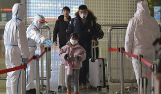 People in protective suits screen travelers at a railway station in Nanjing in eastern China's Jiangsu Province, Tuesday, Feb. 4, 2020. Hong Kong hospitals cut services as medical workers were striking for a second day Tuesday to demand the border with mainland China be shut completely to ward off a virus that caused its first death in the semi-autonomous territory. (Chinatopix via AP)