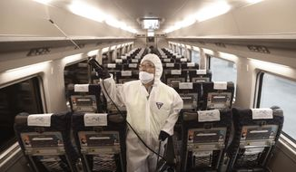 FILE - In this Jan. 24, 2020, file photo, an employee sprays disinfectant on a train as a precaution against a new coronavirus at Suseo Station in Seoul, South Korea. Halting the spread of a new virus that has killed hundreds in China is difficult in part because important details about the illness and how it spreads are still unknown. (AP Photo/Ahn Young-joon, File)
