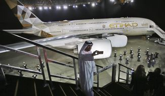 FILE- In this Thursday, Dec. 18, 2014 file photo, an Emirati man takes a selfie in front of a new Etihad Airways A380 in Abu Dhabi, United Arab Emirates. Abu Dhabi's long-troubled Etihad Airways said Tuesday, Feb. 4 2020,  it would sell 38 aircraft to an investment firm and a leasing company in a deal valued at $1 billion, the latest cost-cutting measure by the United Arab Emirates' national carrier. (AP Photo/Kamran Jebreili, File)