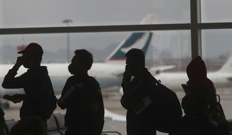 People wearing masks line up for departure at Hong Kong airport in Hong Kong, Tuesday, Feb. 4, 2020. Hong Kong on Tuesday reported its first death from a new virus, a man who had traveled from the mainland city of Wuhan that has been the epicenter of the outbreak. (AP Photo/Achmad Ibrahim)